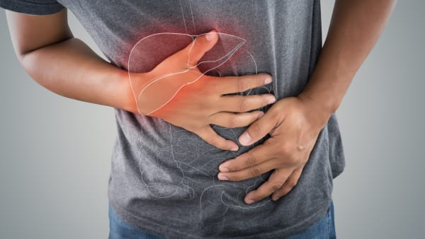 image of person holding hands over their liver and stomach